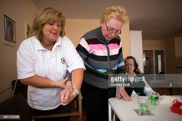 Nurse Doret Kohl holds the arm of day guest Ingrid as she passes the table in the geriatric day care facility of the German Red Cross at Villa...