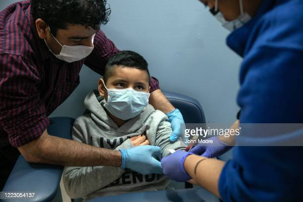 A nurse draws blood for a COVID19 antibody test from Guatemalan immigrant Junior as his father Marvin looks on at a clinic on May 5 2020 in Stamford...