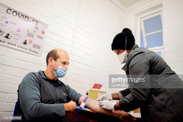 Nurse draws blood from Professor Francois Venter before receiving the experimental vaccine for COVID-19 coronavirus at the Respiratory & Meningeal...