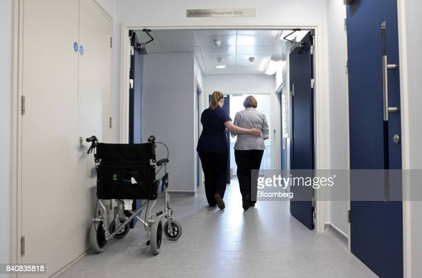 A nurse dressed in a blue uniform lends support to a patient as they walk along a corridor at the BMI Weymouth Hospital in London UK on Thursday Sept...