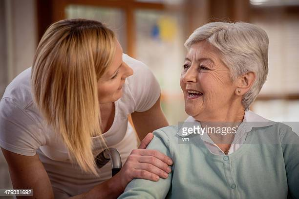 Nurse during home visit with senior woman
