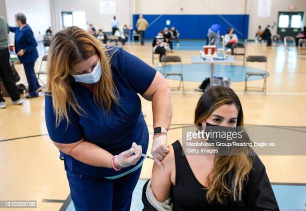 Nurse Elizabeth Johnson administers a dose of COVID-19 vaccine to Melissa Mendez, of Conshohocken. At the Olivet Boys and Girls Club Pendora site in...