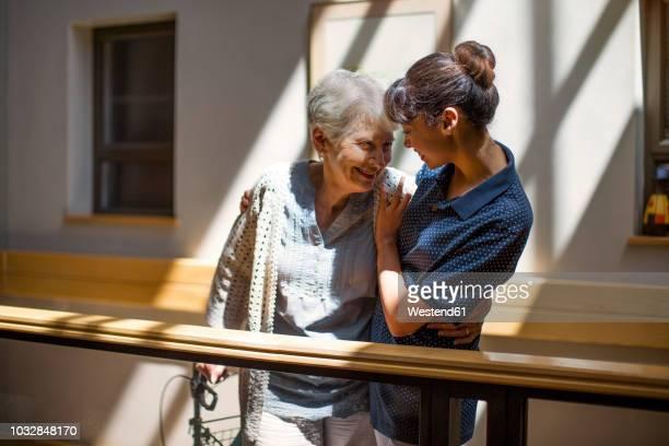 nurse embracing senior woman in retirement home - asistir fotografías e imágenes de stock