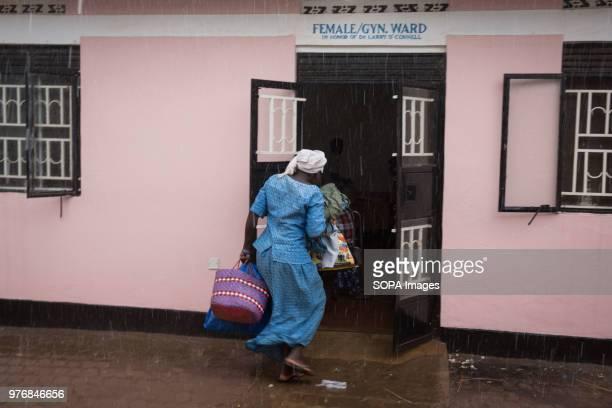 A nurse enters a female ward during a rain shower in Gulu Regional Referral Hospital northern Uganda Medics create prosthetics for some of the...