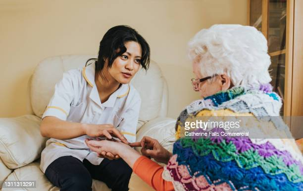 nurse examines an elderly patients painful wrist - human joint stock pictures, royalty-free photos & images