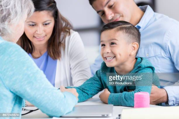 enfermeira examina o garoto em uma clínica comunitária - gratis - fotografias e filmes do acervo