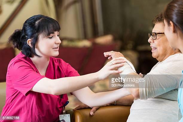 Nurse examines senior woman's wrist
