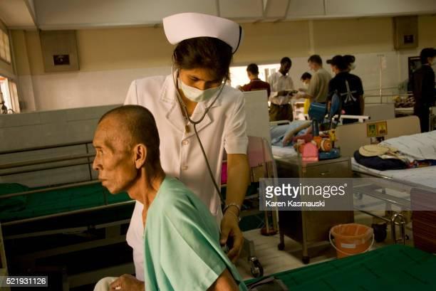 Nurse examining AIDS patient in Thailand