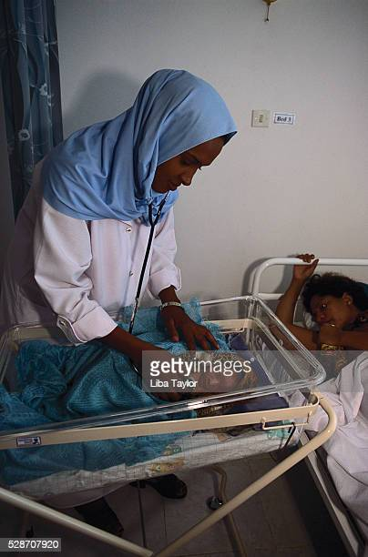 Nurse Examining Newborn next to Mother