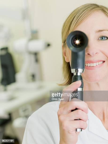 nurse examining patient with opthalmoscope - eye test equipment stock pictures, royalty-free photos & images