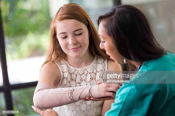 Nurse examining teen patient's broken or injured arm