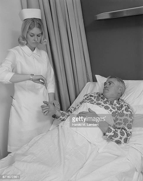 Nurse Examining Temperature Of Patient Using Thermometer