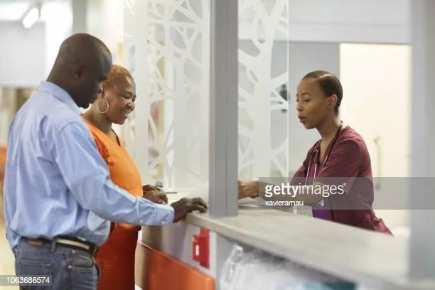 nurse explaining mature couple at reception desk - medical receptionist uniforms stock photos and pictures