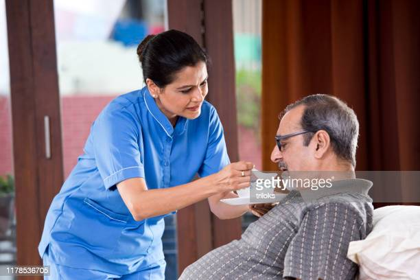 nurse feeding food to old man on bed - ethnicity stock pictures, royalty-free photos & images