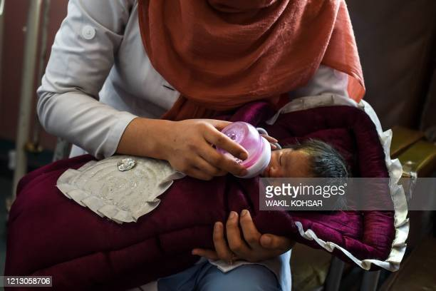 A nurse feeds a newborn baby rescued and brought to Ataturk Children hospital after the mother was killed during a gunmen attack on a maternity...