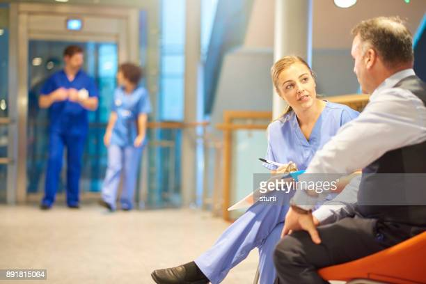 nurse filling out paperwork with patient - outpatient care stock pictures, royalty-free photos & images