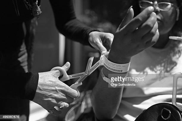 A nurse from Joseph's House removes ID bracelets from HIVpositive Shana ReynoldsFairley's arm after she returned from a recent hospital stay May 3...