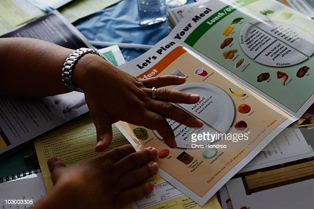 A nurse from New York Presbyterian Hospital goes over nutritional information during a free healthscreening clinic for New York bodega convenience...