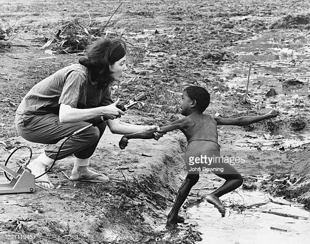 A nurse from the British charity War on Want attempts to vaccinate a terrified boy against cholera during an outbreak of the disease at a refugee...