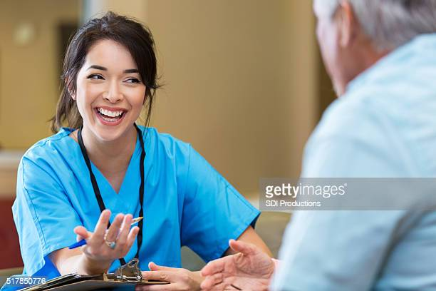 Nurse gestures as she talks with senior male patient