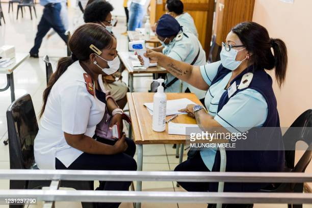 Nurse gets a temperature check before receiving a dose of the Johnson & Johnson vaccine against the COVID-19 coronavirus as South Africa proceeds...
