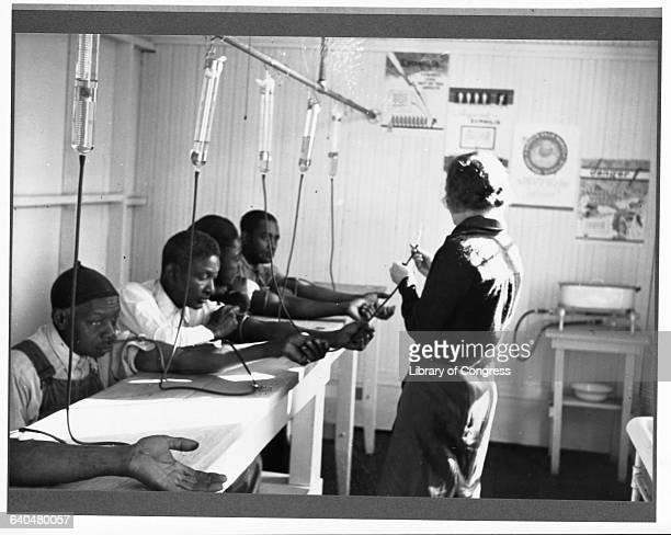 A nurse gives African American men intravenous treatment for venereal disease at a clinic in Georgia