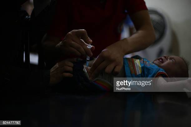 A nurse gives an Hepatitis A vaccines to a child in the vaccine's center belongs to the Syrian Arab Red Crescent Douma branch Picture is taken in Aug...