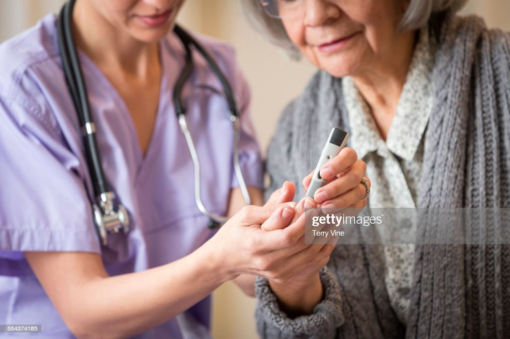 Nurse giving blood sugar test to patient in home : Stock Photo