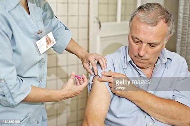 Nurse giving man vaccination