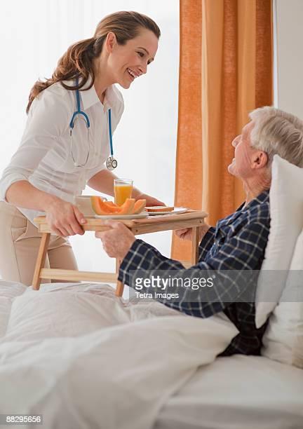 Nurse giving senior man breakfast