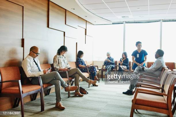 nurse greeting patient in medical office waiting room - healthcare stock pictures, royalty-free photos & images