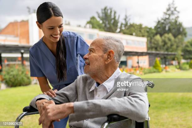 nurse greeting senior patient in the gardens of the hospital - hospice stock pictures, royalty-free photos & images