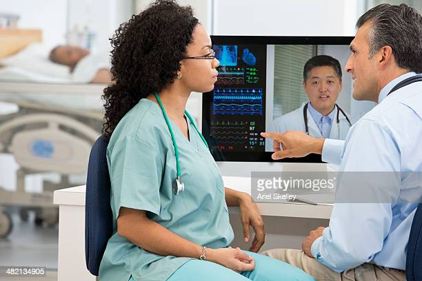 Nurse having teleconference with doctors in hospital