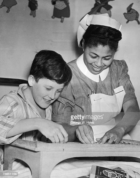 Nurse Hazel Hart from Jamaica helps 13 year-old patient Brian Harris with a jigsaw puzzle at the Princess Alice Hospital, Eastbourne, 7th January...