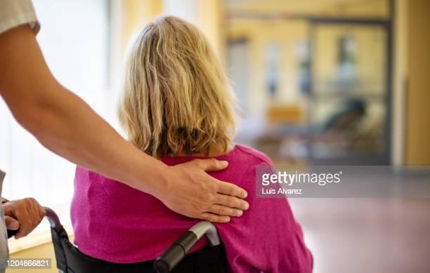 nurse helping a patient in wheelchair - dorso mano foto e immagini stock