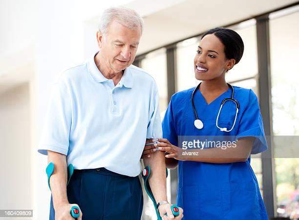 Infirmière aide un patient à béquilles senior