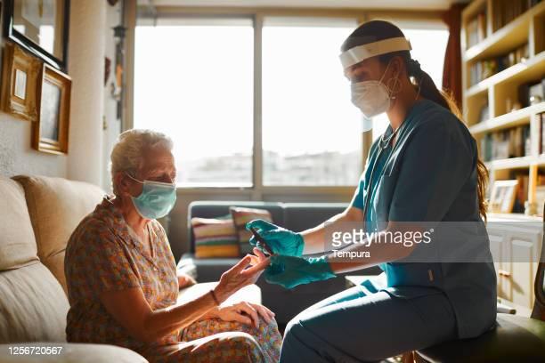 en sjuksköterska som hjälper en äldre kvinna att utföra ett diabetestest - vårdhem bildbanksfoton och bilder