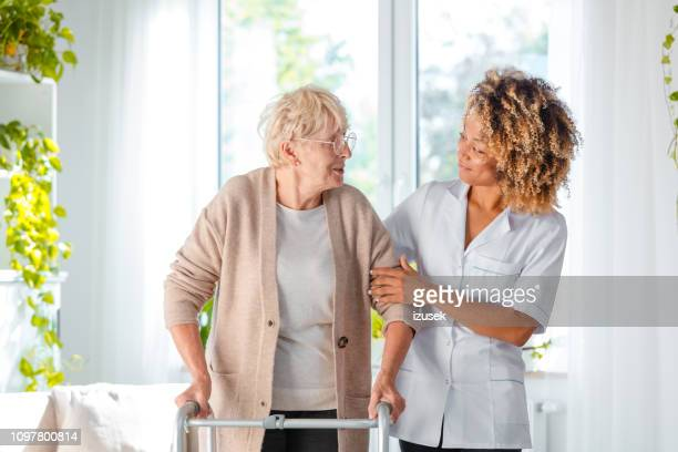 nurse helping an elderly lady in using mobility walker - izusek stock pictures, royalty-free photos & images