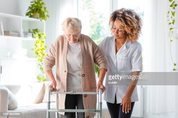 nurse helping an elderly lady in using mobility walker - patient room stock photos and pictures