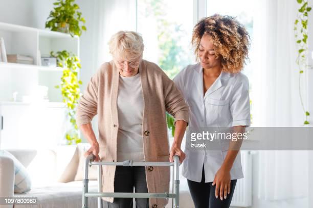 Nurse helping an elderly lady in using mobility walker