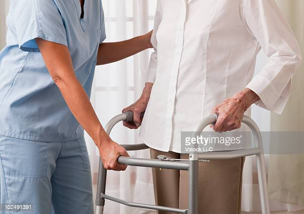Nurse helping an elderly woman use a walker