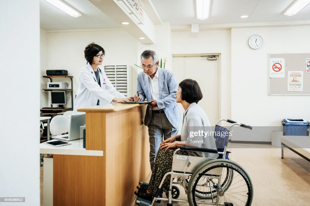 Nurse Helping Elderly Couple At Hospital Counter : Stock Photo