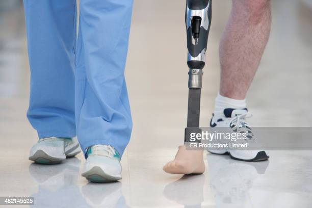 Nurse helping man walk with prosthetic leg
