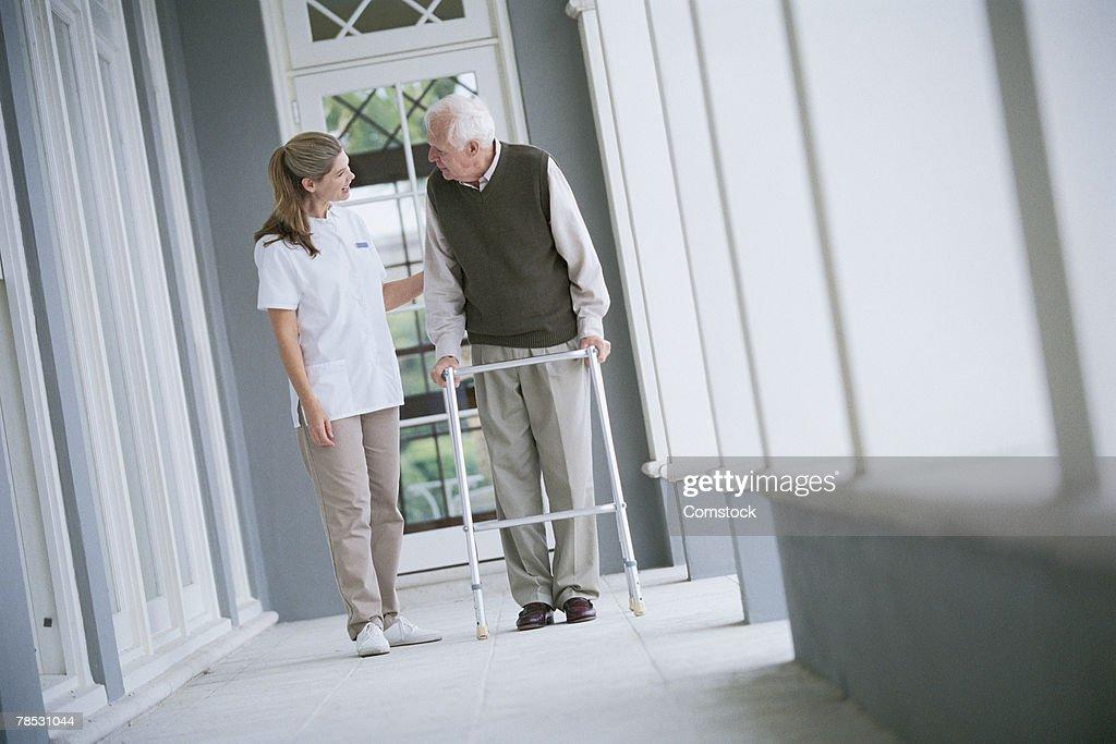 Nurse helping man with walker : Stock Photo