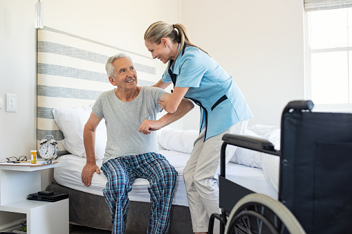 Nurse helping old patient get up 1029340082