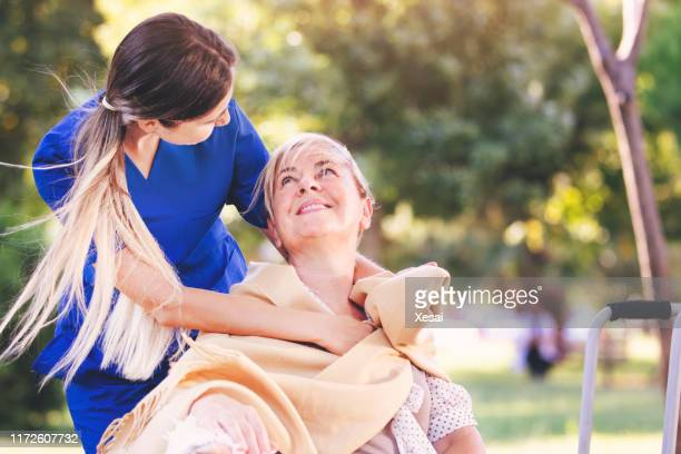nurse helping old woman for comfort and care - hospice stock pictures, royalty-free photos & images
