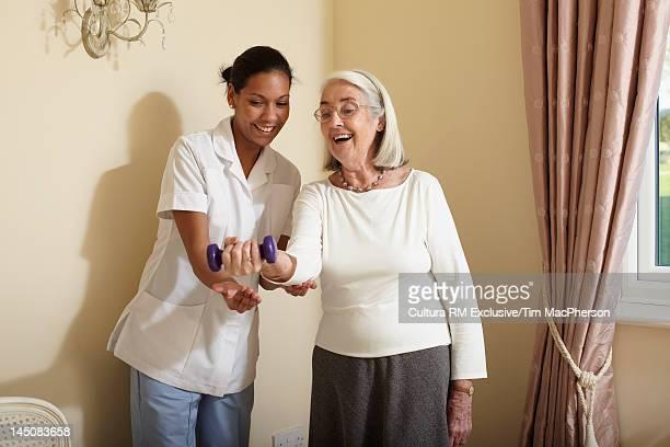Nurse helping older woman exercise
