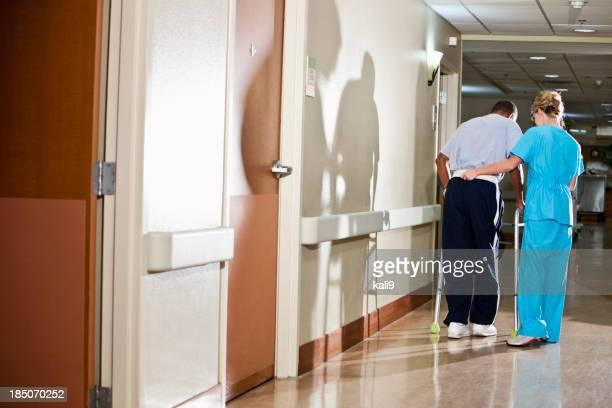 Nurse helping patient walk down hospital corridor