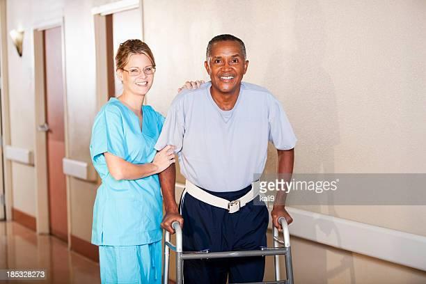 infirmière aide patient de l'hôpital marche le long du couloir - down blouse photos et images de collection