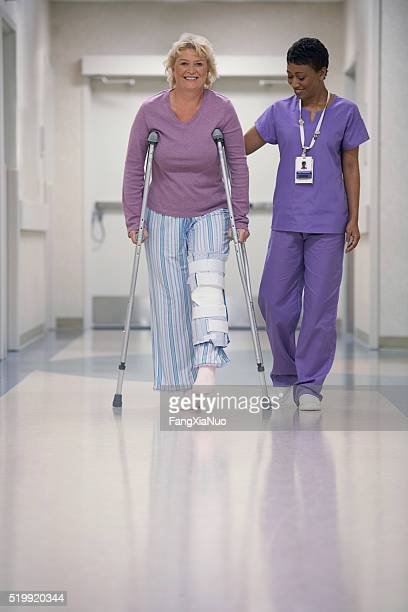 Nurse helping patient with crutches